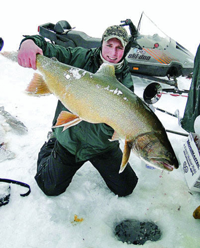 image of angler on ice with giant Lake Trout