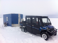 image of ATV trailering a wheel house ice fishing shelter