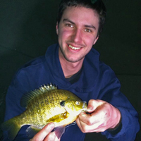 image of ice fisherman holding sunfish