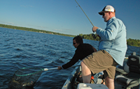 image of Glenn and Jen Fraze netting Pokegama Lake Walleye