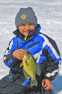 image of ice fishing kid holding crappie