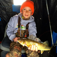 image of Dylan Kukkonen with Walleye in ice fishing shelter
