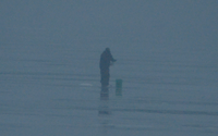 image of an ice fisherman standing in the fog