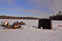 image of snowmobiles and portable shelter on ice