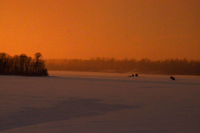 image of ice fishing shelters at sunset