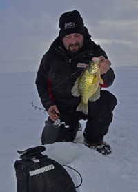 image of Zach Dagel holding Crappie on ice