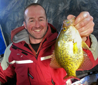 image of Mike Plackner holding Crappie on ice fishing trip