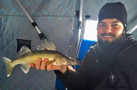 image of ice fisherman holding walleye