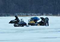 image of snowmobiles rigged with portable ice fishing shelters