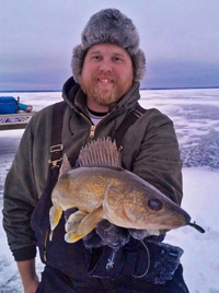 image of Austin Jones holding Walleye on The ice at Lake Winnie