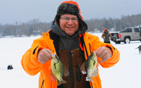 image of ice fisherman holding 2 crappies