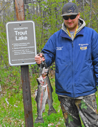 image of Jesse Clusiau with 2 rainbow trout