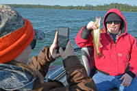 image of laura potter taking photo od dad with walleye